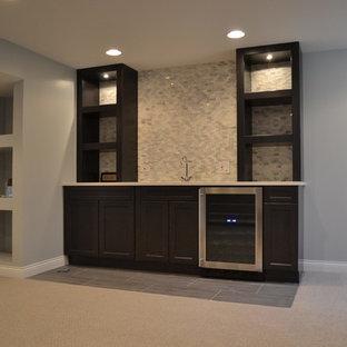Modelo de sótano en el subsuelo clásico, grande, con paredes beige, moqueta, estufa de leña, marco de chimenea de ladrillo y suelo beige