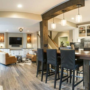Basement - mid-sized rustic look-out medium tone wood floor and gray floor basement idea in Columbus with beige walls and no fireplace