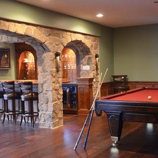 Cette image montre un grand sous-sol traditionnel donnant sur l'extérieur avec un mur vert, un sol en bois foncé, une cheminée standard, un manteau de cheminée en pierre et un sol marron.