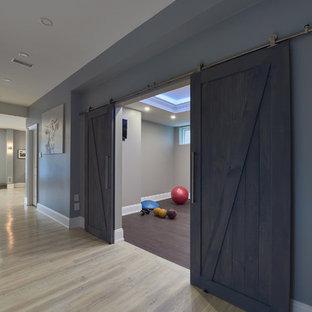 Réalisation d'un sous-sol tradition donnant sur l'extérieur avec un mur gris, un sol en bois clair, une cheminée ribbon et un manteau de cheminée en pierre.