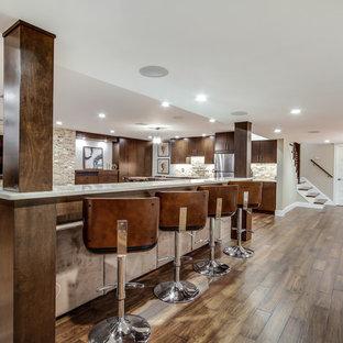 Inspiration pour un grand sous-sol design semi-enterré avec un mur beige, aucune cheminée et un sol en bois foncé.