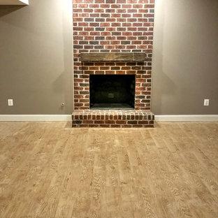 Réalisation d'un grand sous-sol design donnant sur l'extérieur avec un mur gris, un sol en carrelage de porcelaine, une cheminée standard et un manteau de cheminée en brique.