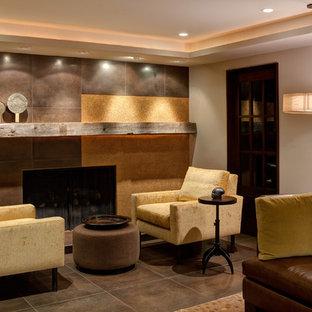 Idée de décoration pour un sous-sol design enterré avec un mur beige, une cheminée standard, un manteau de cheminée en carrelage, un sol en carrelage de céramique et un sol marron.