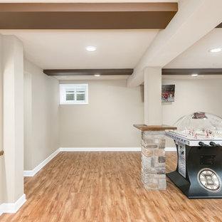 Inspiration pour un grand sous-sol chalet semi-enterré avec un mur gris, un sol en bois brun, une cheminée standard, un manteau de cheminée en pierre et un sol beige.