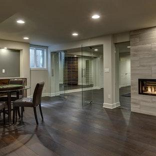Idées déco pour un très grand sous-sol contemporain semi-enterré avec un mur gris, un sol en bois foncé, une cheminée ribbon, un manteau de cheminée en carrelage et un sol marron.