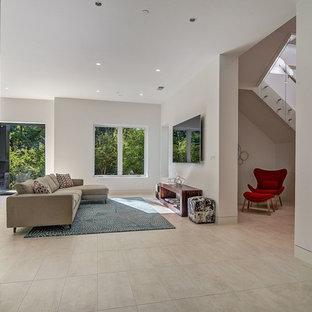 Idée de décoration pour un grand sous-sol design donnant sur l'extérieur avec un mur blanc, un sol en calcaire, une cheminée standard, un manteau de cheminée en pierre et un sol beige.