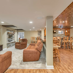 Example of a large mountain style look-out medium tone wood floor and beige floor basement design in Chicago with gray walls, a standard fireplace and a stone fireplace