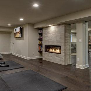 デンバーの巨大なコンテンポラリースタイルのおしゃれな地下室 (半地下 (窓あり) 、グレーの壁、濃色無垢フローリング、横長型暖炉、タイルの暖炉まわり、茶色い床) の写真