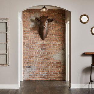 Exemple d'un grand sous-sol industriel donnant sur l'extérieur avec un mur gris, un sol en vinyl, une cheminée d'angle, un manteau de cheminée en brique et un sol marron.