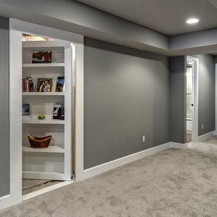 Cette image montre un sous-sol traditionnel semi-enterré et de taille moyenne avec un mur gris, moquette, une cheminée standard, un manteau de cheminée en pierre et un sol gris.