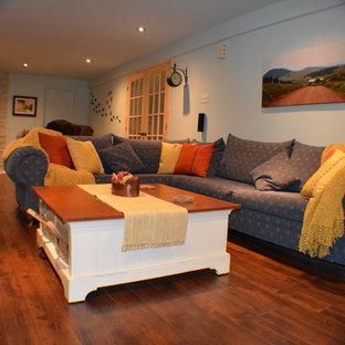 Idées déco pour un sous-sol méditerranéen de taille moyenne avec un mur bleu, un sol en bois foncé, un poêle à bois et un manteau de cheminée en pierre.