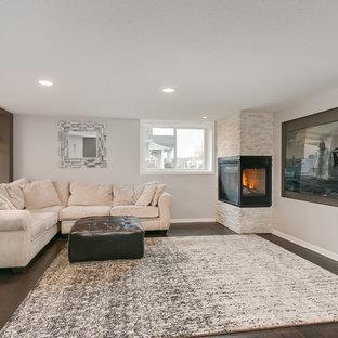 Réalisation d'un grand sous-sol tradition donnant sur l'extérieur avec un mur gris, un sol en bois foncé, une cheminée d'angle, un manteau de cheminée en carrelage et un sol marron.