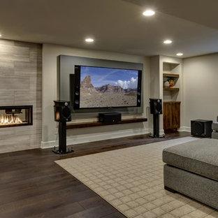 Exemple d'un très grand sous-sol tendance semi-enterré avec un mur gris, un sol en bois foncé, une cheminée ribbon, un manteau de cheminée en carrelage, un sol marron et salle de cinéma.