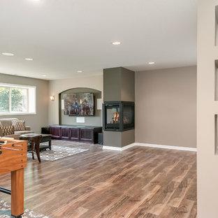 Idées déco pour un sous-sol classique semi-enterré et de taille moyenne avec un mur beige, un sol en bois brun, une cheminée double-face, un manteau de cheminée en plâtre et un sol marron.