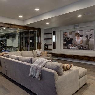 На фото: большой подвал в стиле современная классика с наружными окнами, серыми стенами, паркетным полом среднего тона, бежевым полом и домашним кинотеатром без камина с
