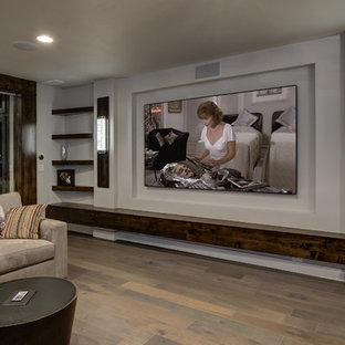 Idée de décoration pour un grand sous-sol tradition semi-enterré avec un mur gris, un sol en bois brun, aucune cheminée et un sol beige.