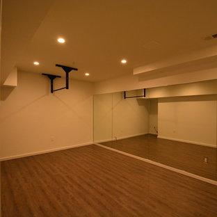 Idées déco pour un très grand sous-sol classique donnant sur l'extérieur avec un mur beige, un sol en bois foncé et aucune cheminée.