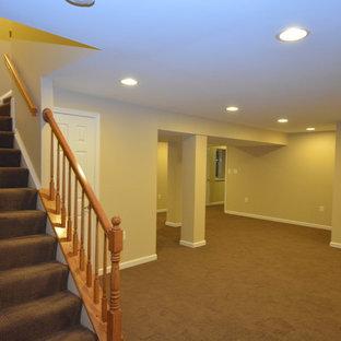 Réalisation d'un grand sous-sol tradition donnant sur l'extérieur avec un mur jaune, moquette, aucune cheminée et un sol marron.