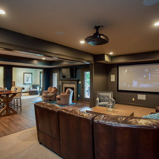Large mountain style walk-out carpeted basement photo in Orange County with black walls