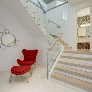 Cette photo montre un grand sous-sol tendance donnant sur l'extérieur avec un mur blanc, un sol en calcaire, une cheminée standard, un manteau de cheminée en pierre et un sol beige.