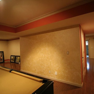 Cette photo montre un sous-sol chic enterré et de taille moyenne avec un mur orange, un sol en bois brun, une cheminée standard, un manteau de cheminée en pierre et un sol marron.