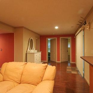 Immagine di una taverna chic interrata di medie dimensioni con pareti arancioni, pavimento in legno massello medio, camino classico, cornice del camino in pietra e pavimento marrone