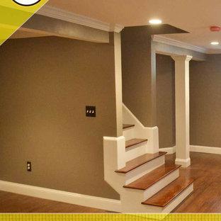Idées déco pour un grand sous-sol classique enterré avec un mur gris, un sol en bois foncé et aucune cheminée.