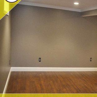Cette image montre un grand sous-sol traditionnel enterré avec un mur gris, un sol en bois foncé et aucune cheminée.