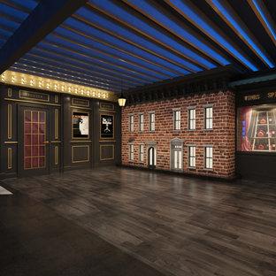 Réalisation d'un grand sous-sol design enterré avec un mur noir, un sol en bois foncé et aucune cheminée.
