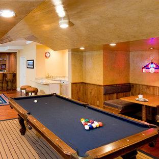 Immagine di un'ampia taverna classica interrata con pareti beige, pavimento in legno massello medio e pavimento arancione