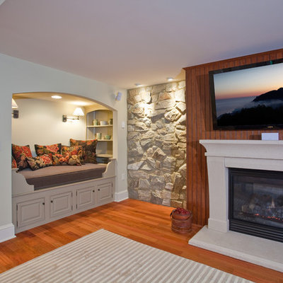 Example of a large classic walk-out medium tone wood floor basement design in Philadelphia with a standard fireplace and a stone fireplace