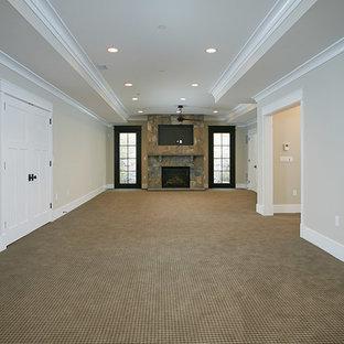 Cette photo montre un grand sous-sol craftsman donnant sur l'extérieur avec un mur beige, moquette, une cheminée standard et un manteau de cheminée en pierre.