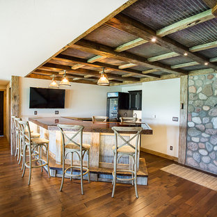 Example of a large mountain style walk-out dark wood floor basement design in Other with white walls, a standard fireplace and a stone fireplace