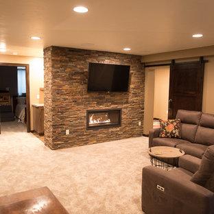 Réalisation d'un sous-sol design enterré avec un mur beige, moquette, une cheminée double-face, un manteau de cheminée en pierre et un sol blanc.