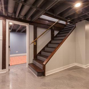 Inspiration pour un sous-sol minimaliste semi-enterré et de taille moyenne avec un mur gris, béton au sol, aucune cheminée et un sol bleu.