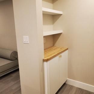 Cette photo montre un sous-sol tendance donnant sur l'extérieur avec un mur blanc, un sol en vinyl, un poêle à bois, un manteau de cheminée en carrelage et un sol gris.