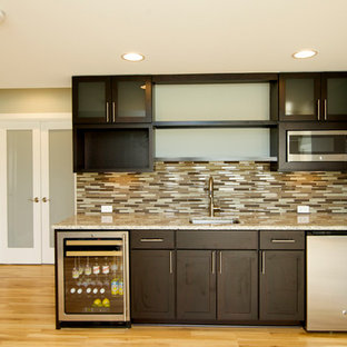 Réalisation d'un très grand sous-sol minimaliste donnant sur l'extérieur avec un mur vert et un sol en bois brun.
