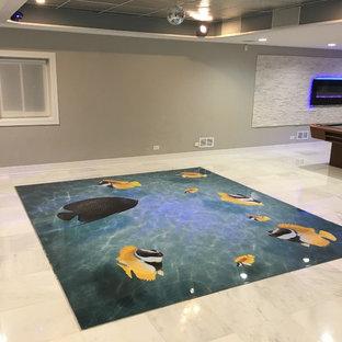 Cette photo montre un grand sous-sol moderne donnant sur l'extérieur avec un mur gris, un sol en marbre, un manteau de cheminée en pierre et une cheminée ribbon.