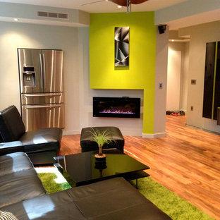 Idee per una taverna contemporanea con pareti verdi, pavimento in legno massello medio, camino lineare Ribbon e pavimento arancione