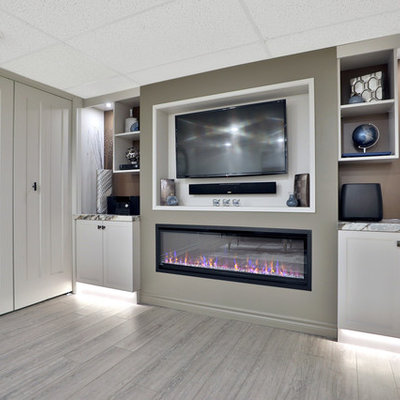 Example of a mid-sized trendy underground vinyl floor and gray floor basement design in Toronto with gray walls, a standard fireplace and a plaster fireplace