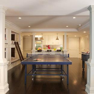 Cette image montre un très grand sous-sol traditionnel donnant sur l'extérieur avec un mur gris et un sol en bois foncé.