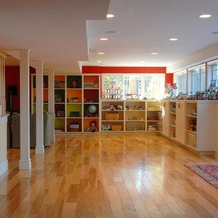 Inspiration pour un sous-sol traditionnel semi-enterré avec un mur rouge, aucune cheminée, un sol en bois clair et un sol orange.