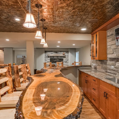 Basement - large rustic look-out medium tone wood floor and beige floor basement idea in Chicago with gray walls, a standard fireplace and a stone fireplace