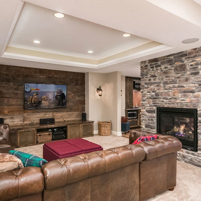 Basement - mid-sized rustic walk-out medium tone wood floor and brown floor basement idea in Minneapolis with beige walls, a two-sided fireplace and a stone fireplace