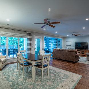 Aménagement d'un grand sous-sol classique donnant sur l'extérieur avec un bar de salon, un mur gris, un sol en vinyl et un sol marron.