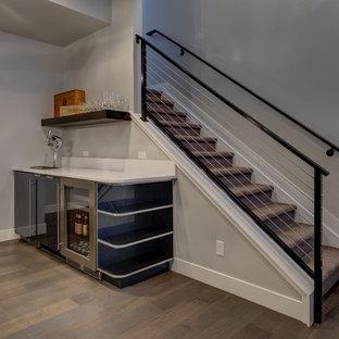 Idéer för en stor klassisk källare utan ingång, med grå väggar, mellanmörkt trägolv och beiget golv