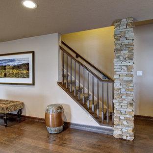 Aménagement d'un petit sous-sol classique semi-enterré avec un mur bleu, un sol en carrelage de porcelaine, une cheminée d'angle, un manteau de cheminée en pierre et un sol beige.