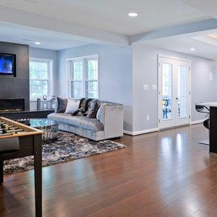Idée de décoration pour un grand sous-sol design donnant sur l'extérieur avec un mur bleu, une cheminée standard, un manteau de cheminée en pierre et un sol marron.
