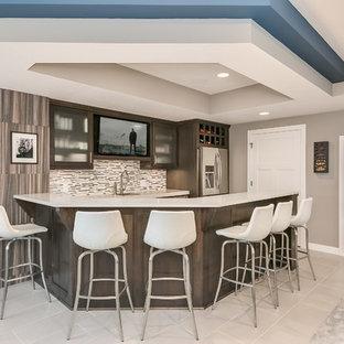 Cette photo montre un grand sous-sol tendance semi-enterré avec un mur gris, moquette, une cheminée d'angle, un manteau de cheminée en carrelage et un sol gris.