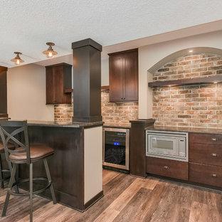 Inspiration pour un grand sous-sol traditionnel donnant sur l'extérieur avec un mur gris, un sol en bois brun, une cheminée ribbon, un manteau de cheminée en métal et un sol marron.